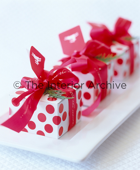 Red and white polka dot boxes make great decorations for Christmas party favours that can also be used as place settings on the dining table