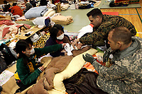U.S. Navy Lt. Cmdr. Ewell Hollis, a physician with III Marine Expeditionary Force (Fwd), examines a Japanese woman, here March 21, who broke her arm during the tsunami. Service members with U.S. Forces Japan (Fwd) and Japanese Ground Self-Defense Forces surveyed the school and made plans to establish power, food and water supply lines. The school is being utilized as an internally displaced persons camp for residents affected by the earthquake and subsequent tsunami that struck mainland Japan March 11, causing widespread damage. As part of Operation Tomodachi, U.S. Forces Japan stands ready to support our Japanese partners and to provide assistance when called upon.