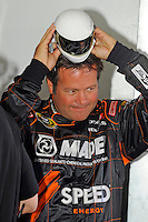 Robby Gordon (#7) tries on a toy helmet on for size in the garage.