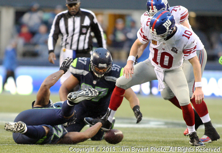 Seattle Seahawks defensive end Michael Bennett (72) and defensive tackle Jordan Hill (97) go for a fumble dropped by New York Giants quarterback Eli Manning (10) at CenturyLink Field in Seattle, Washington on November 9, 2014. The Seahawks  beat the Giants 38-17. ©2014. Jim Bryant Photo. All rights Reserved.
