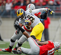 Ohio State Buckeyes defensive back Vonn Bell (11) and Ohio State Buckeyes defensive tackle Michael Bennett (63) take down Michigan Wolverines quarterback Devin Gardner (98) in the 1st quarter of their game at Ohio Stadium in Columbus, Ohio on November 29, 2014.  (Dispatch photo by Kyle Robertson)
