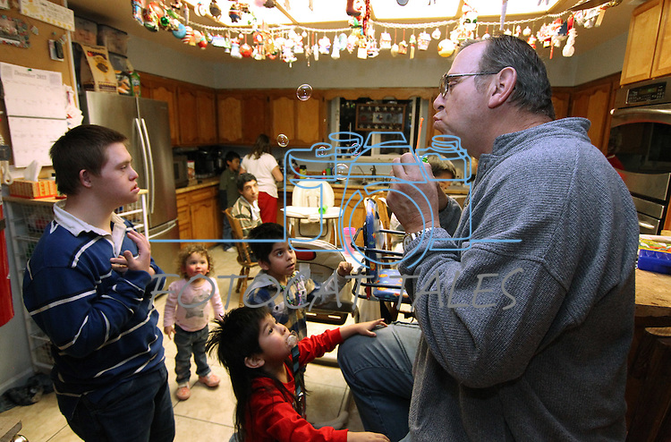Merrill Simon blows bubbles to entertain his kids while they wait for dinner in Mound House, Nev., on Monday, Dec. 19, 2011. Merrill and his wife Roberta have adopted 21 special-needs children over the past 30 years..Photo by Cathleen Allison