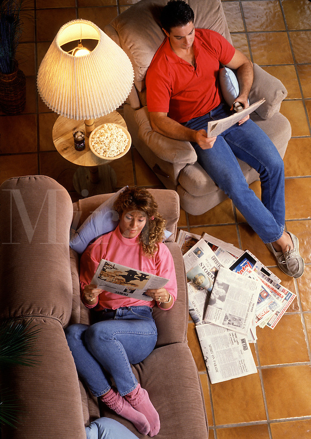 Overhead view of a young couple relaxing and reading the newspaper in their home.