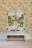 An antique painted cabinet decorated with a Japanese scene stands against a floral patterned wallpaper