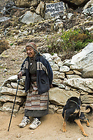 Portrait of Dhaki - 76 year old lady with the dog, carrying potatoes from her own field in Pangboche to Milinggo.<br /> Lives in the Tengboche nunnery.