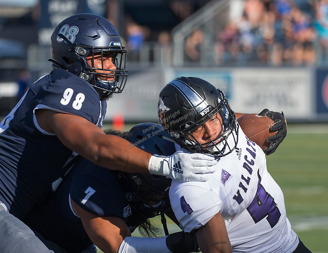 Weber State's Kevin Smith Jr (4) is brought down by the Nevada defense in the Nevada vs Weber State football game in Reno, Nevada on Saturday, Sept. 14, 2019.