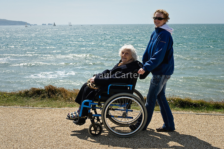 Elderly woman with her carer  at Milford-on-Sea enjoy the sunshine and views across the sea.