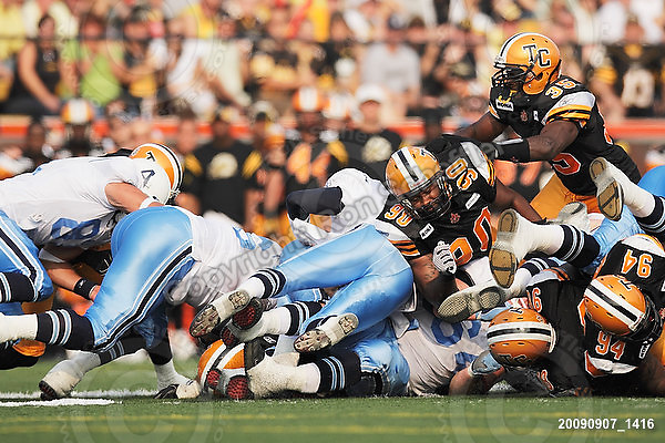 September 7, 2009; Hamilton, ON, CAN; Hamilton Tiger-Cats defensive lineman Demonte' Bolden (90) linebacker Otis Floyd (35) try to stop Toronto Argonauts quarterback Cody Pickett (3). CFL football - the Labour Day Classic - Toronto Argonauts vs. Hamilton Tiger-Cats at Ivor Wynne Stadium. The Tiger-Cats defeated the Argos 34-15. Mandatory Credit: Ron Scheffler.