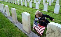 Maddie Powers, 9, a Brownie with Troop 2238 in Mountlake Terrace, plants a flag amongst the grave markers at the Veterans Memorial Cemetery within Evergreen-Washelli Cemetery in Seattle Sunday, Nov. 11, 2007. Powers and other girl scouts visited the over 5000 markers after taking part in the 58th Annual Veterans Day Service of Remembrance at the cemetery. (Photo by Andy Rogers).