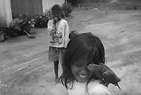 BRAZIL,El DORADO DOS CARAJAS : Children playing in front of their houses, with parrot at Landless Workers Movement camp on 17 April, 1998  at transamazonica in Parauapebas south of Pará, northern Brazil. -  Photo by Paulo Amorim