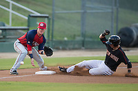 John Ziznewski (5) of the Kannapolis Intimidators slides into third base as Conor Keniry (11) of the Hagerstown Suns fields the throw at Intimidators Stadium on July 18, 2015 in Kannapolis, North Carolina.  The Intimidators defeated the Suns 1-0.  (Brian Westerholt/Four Seam Images)