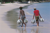 Two fishermen carry their day's catch to the informal fish market on the Seychelles' Beau Vallon Bay beach, where all the local fishing boats pool what they have caught.