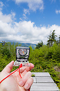 Hiker holding compass on the summit of Mount Hitchcock (North) in the White Mountains, New Hampshire USA.