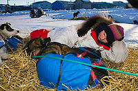 Honorary 2007 Iditarod musher Susan Butcher's daughter Tekla Monson, wearing her mom's mushing outfit & mukluks, lays w/ her dogs at Elim checkpoint