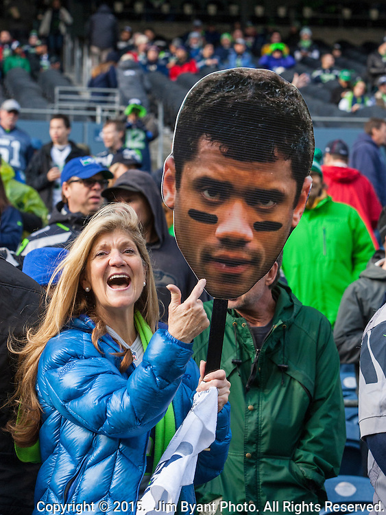 A Seattle Seahawks  fan points to a picture of Russell Wilson before their game against the Green Bay Packers during the NFC Championship game at CenturyLink Field in Seattle, Washington on January 18, 2015.  The Seattle Seahawks beat the Green Bay Packers in overtime 28-22 for the NFC Championship Seattle.  ©2015. Photo by Jim Bryant, All Rights Reserved.