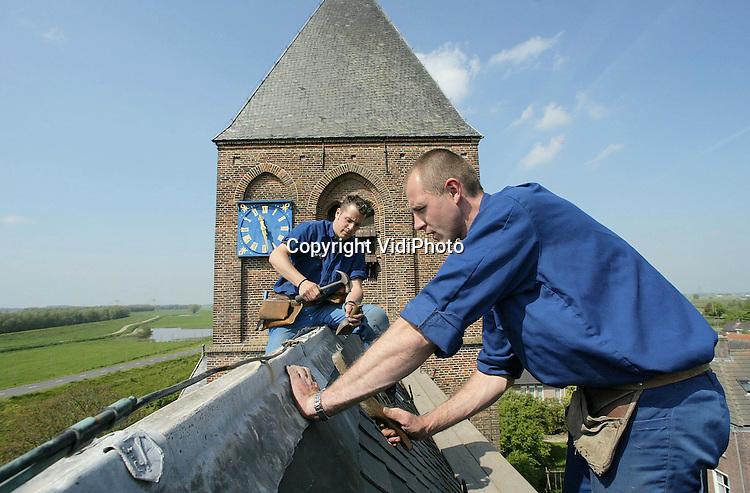 Foto: VidiPhoto..IJZENDOORN - Voorlopig hoeven de kerkgangers in het Betuwse IJzendoorn niet meer te vrezen dat ze kapotte leien op hun hoofd krijgen. Op dit moment wordt door het leidekkersbedrijf Van Wely uit Groessen de hand gelegd aan de het laatste deel van de restauratie van het dak van dit Rijksmonument. Het dak van de kerk was dringend aan vervanging toe omdat de kapotte leien naar beneden vielen en het regenwater naar binnen liep. Kerk en Monumentenzorg hebben gekozen voor een dure en duurzame oud-Duitse leisoort die niet zo veel meer wordt toegepast tijdens restauraties. Het dak moet nu weer 100 jaar mee kunnen.
