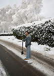 Man holding spade standing in road after clearing snow