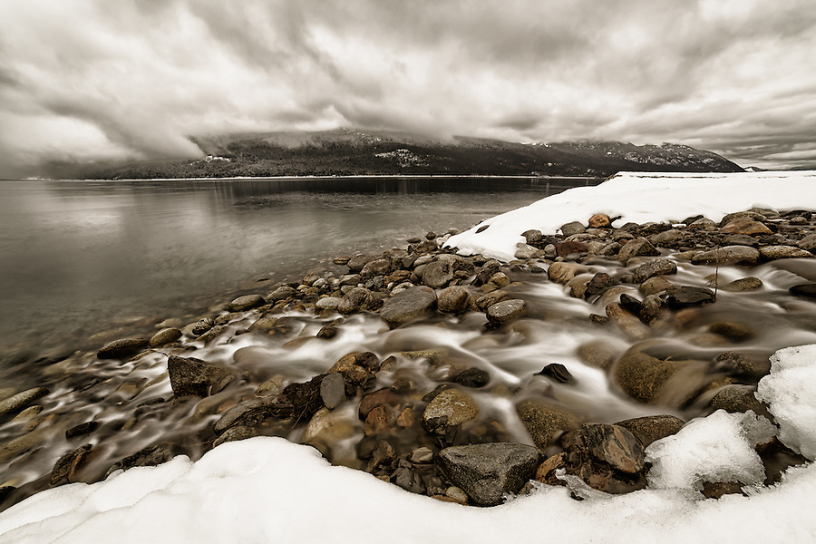 A long exposure softens the water as it flows from a stream into the lake as dramatic clouds loom overhead on a cold winter day in British Columbia, Canada.