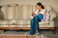 A woman in her early twenties breastfeeding her nine month old baby girl at home while sitting on a sofa in her living room. The baby is playing, putting her fingers in her mother's mouth .<br /> <br /> Image from the breastfeeding collection of the &quot;We Do It In Public&quot; documentary photography picture library project: <br />  www.breastfeedinginpublic.co.uk<br /> <br /> <br /> Dorset, England, UK<br /> 08/03/2013<br /> <br /> &copy; Paul Carter / wdiip.co.uk