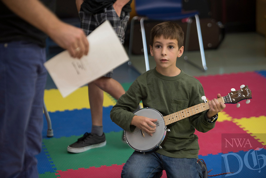 NWA Democrat-Gazette/J.T. WAMPLER Nikolai Margulis, 8, of Fayetteville plays his banjo while working with other children to plan a performance Sunday Oct. 4, 2015 at the Fayetteville Public Library's True Lit. ((SEE 002 FOR MORE INFO))