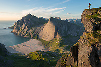 Female hiker takes in view over Bunes beach from isolated mountain peak, Moskenesøy, Lofoten Islands, Norway