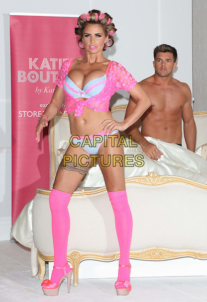 Katie Price (Jordan) & Leandro Penna.The launch photocall for Katie Price's new summer lingerie range for Store 21, The Worx, London, England..May 29th, 2012.full length pink lace top knotted bra cleavage belly stomach midriff knickers underwear tights stockings tattoo garter beige platform sandals shoes rollers curlers in hair bed chest topless couple hands on hips.CAP/ROS.©Steve Ross/Capital Pictures.