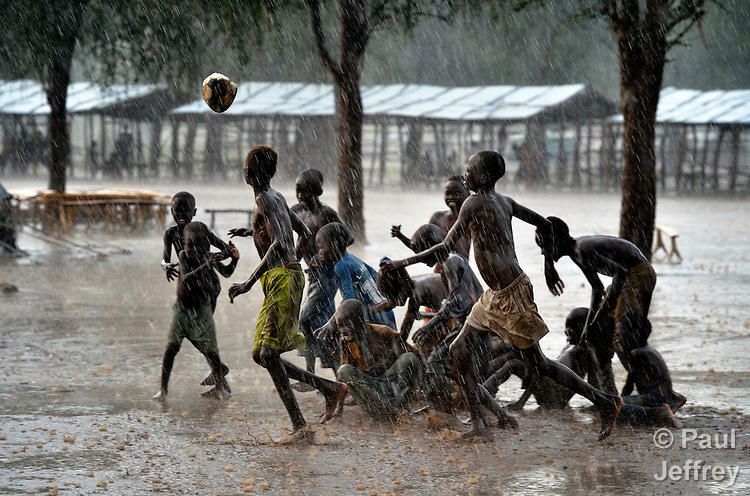 "Children play football during an October 2012 rainstorm in the Doro refugee camp in South Sudan's Upper Nile State. More than 110,000 refugees had come to camps in Maban County from Sudan's Blue Nile region, where the Sudanese military was bombing civilian populations as part of its response to a local insurgency. Under ""informed consent"" rules that require prior approval, the photographer would have had to stop the boys from playing, have them find and identify their parents somewhere in the sprawling camp, explain the intricacies of ""informed consent"" and usage, get their signatures, and then return to photograph the game. That's a process that's allegedly designed to assure that the boys are not depicted in an undignified manner. Photo by Paul Jeffrey."