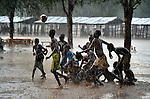 Children play football during an October 2012 rainstorm in the Doro refugee camp in South Sudan's Upper Nile State. More than 110,000 refugees had come to camps in Maban County from Sudan's Blue Nile region, where the Sudanese military was bombing civilian populations as part of its response to a local insurgency.