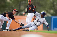 GCL Rays outfielder Miguel Hernandez (14) slides into second as Ryan Mountcastle (43) applies the tag with Alejandro Juvier (16) looking on during the first game of a doubleheader against the GCL Orioles on August 1, 2015 at the Ed Smith Stadium in Sarasota, Florida.  GCL Orioles defeated the GCL Rays 2-0.  (Mike Janes/Four Seam Images)
