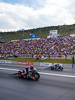 Jul. 18, 2014; Morrison, CO, USA; NHRA pro stock motorcycle rider Andrew Hines (near lane) races alongside Eddie Krawiec during qualifying for the Mile High Nationals at Bandimere Speedway. Mandatory Credit: Mark J. Rebilas-