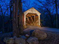 The Cox Ford Bridge over Sugar Creek is shown here at dusk with lights on and in the bridge.  Parke County, Indiana