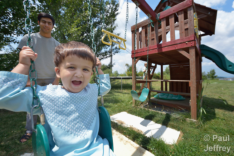 Sanaullah Ahmadzai, 2, gets a push from his father, Ahmadullah Ahmadzai, in the yard of their home in Harrisonburg, Virginia. Refugees from Afghanistan, they were resettled in Harrisonburg by Church World Service.<br /> <br /> Photo by Paul Jeffrey for Church World Service.