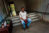 A Cuban barber waits for customers in an improvised barber shop in the entrance to an apartment block in Bahía, a public housing suburb of Havana, Cuba, 11 February 2011.