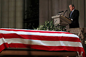 Former President George W. Bush pauses as he speaks in front of the flag-draped casket of his father, former President George H.W. Bush, at the State Funeral at the National Cathedral, Wednesday, Dec. 5, 2018, in Washington.<br /> Credit: Alex Brandon / Pool via CNP
