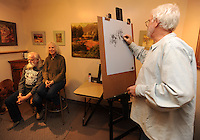 NWA Media/ANDY SHUPE - Artist MM Kent, right, uses charcoal Saturday, Dec. 6, 2014, to sketch Hank and Jo Barnes of War Eagle during the Quick Draw drawing event at the Fayetteville Underground. The event allowed visitors to come and model, draw or observe during a period meant for instruction and enjoyment.