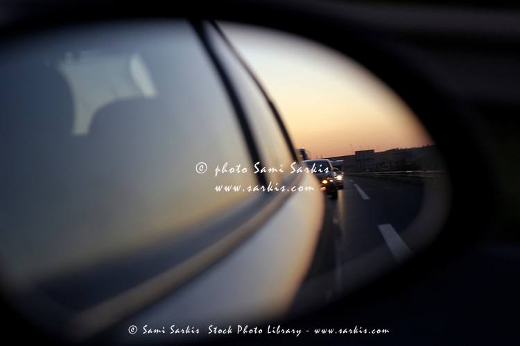 Left side rear view mirror reflecting traffic on the highway.
