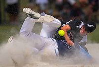NZ's Cole Evans tries to tag Alan Pekar during the Challenge Cup TAB international men's softball final between the NZ Black Sox and Argentina at the AWF Sports Stadium in Albany, New Zealand on Sunday, 12 February 2017. Photo: Dave Lintott / lintottphoto.co.nz
