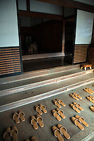 "Japanese Slippers carefully placed for guests arrival at ""engawa"" or entrance.  Visitors to Japanese homes and temples are required to remove their shoes at the entrance, replacing them with hallway slippers such as these before entering.  Many young Japanese are happy to ignore the slippers and just walk around in ther sock or barefoot except in colder months."