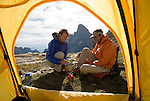 A young couple cooks dinner while camping in the high alpine of the Teton Range, Wyoming.