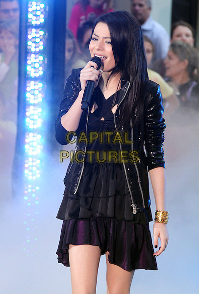 "MIRANDA COSGROVE .performs live on NBC's ""TODAY"" Show at Rockefeller Center, New York, NY, USA, 6th September 2010..half length music live on stage performing concert gig black leather jacket  microphone singing tiered ruffle dress gold bracelet .CAP/ADM/AC.©Alex Cole/AdMedia/Capital Pictures."