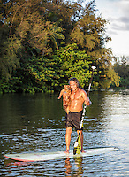 Hawaiian carver Keoni Durant and his Pomeranian dog Milo on a standup paddleboard, Hanalei River, Kaua'i.