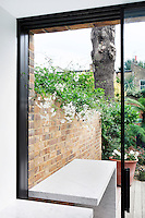 A view through an open sliding glass door that leads out onto a decked terrace. A marble shelf unit provides a useful table space when dining outdoors.