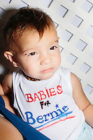 """A baby wears a shirt saying """"Babies for Bernie"""" as Vermont senator and Democratic presidential candidate Bernie Sanders speaks at a campaign event at the White Mountain Chalet event hall in Berlin, New Hampshire."""
