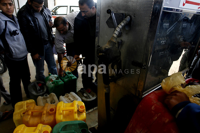 Palestinians wait to fill containers with fuel at a petrol station in Khan Younis in the southern Gaza Strip March 8, 2012. Palestinian Islamist group Hamas faces growing discontent in its Gaza stronghold because of renewed tax hikes and the mismanagement of a power crisis that has led to lengthy blackouts across the coastal enclave. Traders who import goods from Israel and the West Bank say Hamas authorities have introduced additional fees beyond the usual tax they collect, putting their businesses at risk and threatening the livelihoods of thousands of workers. Photo by Abed Rahim Khatib