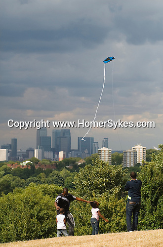 Black British family playing together. Father older son flying kite, and young children a boy and girl. Canary Whaft London skyline. UK
