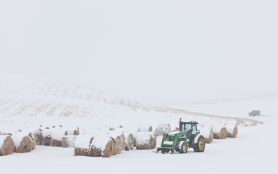 A green John Deere tractor sits near round hay bales during a winter snowstorm in Washington State.