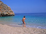 Model Released Young boy on the beach skimming stones in the sea, Sicily, Itlay