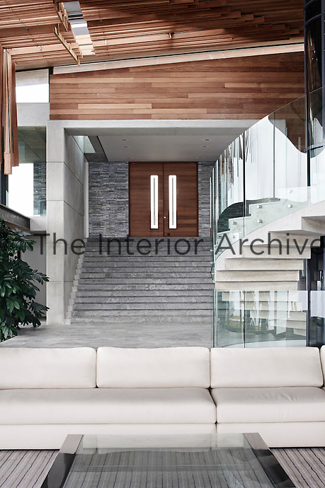 A Hollywood-style grand staircase pulls down from the elevated entrance to the lower living level, which holds the kitchen, dining room and living room. The primary ideas was a single roof enclosing one living space broken up by furniture clusters and carpeting to define the spaces. The family's two small kids made safety a priority and all elevated surfaces have security glass railings.