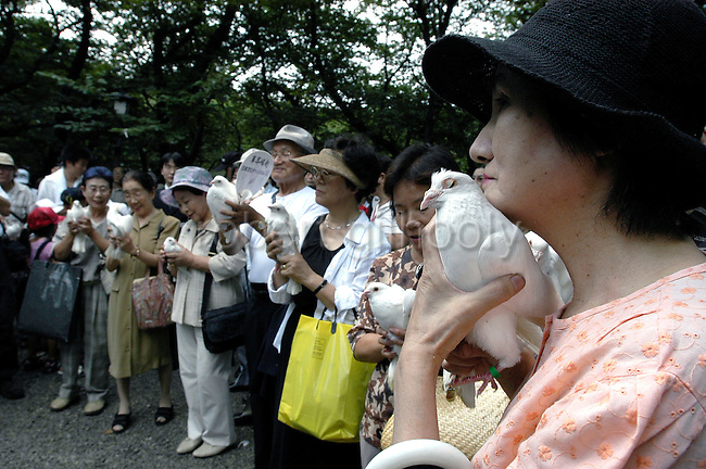 Visitors holds white doves, dozens of which are set free as a symbol of peace at Yasukuni Shrine in Tokyo, Japan. very year on August 15, the day Japan officially surrendered in WWII, tens of thousands of Japanese visit the controversial shrine to pay their respects to the 2.46 million war dead enshrined there, the majority of which are soldiers and others killed in WWII and including 14 Class A convicted war criminals, such as Japan's war-time prime minister Hideki Tojo. Each year speculation escalates as to whether the country's political leaders will visit the shrine, the last to do so being Junichiro Koizumi in 2005. Nationalism in Japan is reportedly on the rise, while sentiment against the nation by countries that suffered from Japan's wartime brutality, such as China, has been further aggravated by Japan's insistence on glossing over its wartime atrocities in school text books...Photographer:Robert Gilhooly..