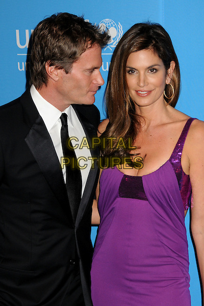 RANDE GERBER & CINDY CRAWFORD.UNICEF Ball 2009 Honoring Jerry Weintraub held at the Beverly Wilshire Hotel, Beverly Hills, California, USA..December 10th, 2009.half length dress black suit profile married husband wife gold hoop earrings  purple sequins sequined .CAP/ADM/BP.©Byron Purvis/AdMedia/Capital Pictures.